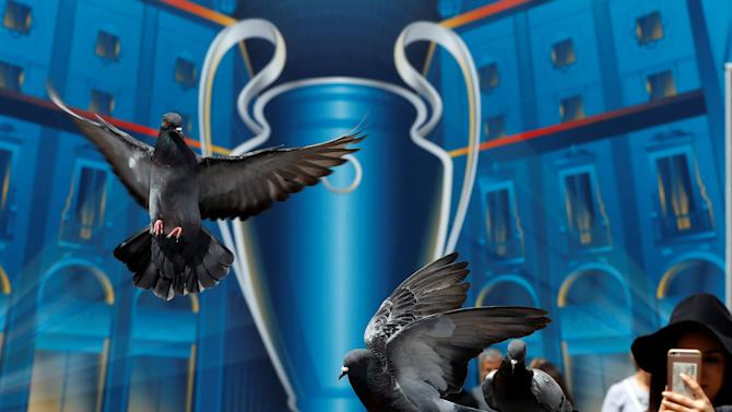 Pigeons fly in front of the UEFA Champions League poster at the Duomo square in Milan