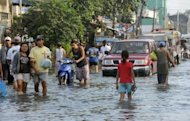 Philippine commuters maneuver through floodwaters in Calumpit town, 50 kilometres north of Manila. As floods which have swamped parts of the Philippines and affected more than two million people extend into their second week, the dead and the living are sharing premium space on dry ground
