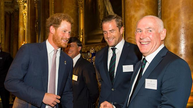 Britain's Prince Harry speaks to Ireland Rugby Union player Jamie Heaslip and team manager Mick Kearney at a Rugby World Cup reception at Buckingham Palace