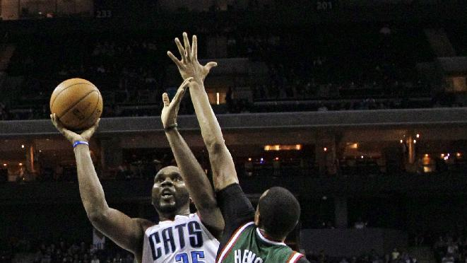 Charlotte Bobcats' Al Jefferson (25) shoots over Milwaukee Bucks' John Henson (31) during the second half of an NBA basketball game in Charlotte, N.C., Monday, Dec. 23, 2013. The Bobcats won 111-110 in overtime