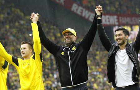 Borussia Dortmund's coach Klopp celebrates with Marco Reus and Sahin after their team's first division Bundesliga soccer match against Werder Bremen in Dortmund