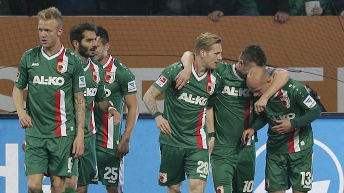 Augsburg's Tobias Werner, right,  celebrates with team mates after scoring his side's opening goal during the German first division Bundesliga soccer match between FC Augsburg and FC Schalke 04, in Augsburg, southern Germany, Friday, March 14, 2014
