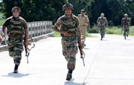 Indian soldiers run across a bridge towards burning houses at Nelibari village in the northeastern state of Assam. Large troop deployments appear to have stemmed an outburst of ethnic violence in northeast India, after a week of clashes that left at least 45 people dead