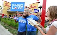 """A couple kiss in front of a Chick-fil-A fast food restaurant in Hollywood as a Christian activist reads passages from the Bible on August 3, in Hollywood, California. Gays and lesbians puckered up in protest Friday, staging """"kiss-ins"""" outside Chick-fil-A outlets across the United States over the fast food chain's opposition to same-sex marriage"""