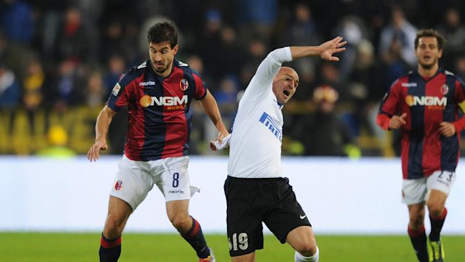 Bologna's Gyrgy Garics, left, fouls Inter's Esteban Cambiasso during the Italian Serie A soccer match between Bologna and Inter Milan at the Renato Dall' Ara stadium in Bologna, Italy, Sunday, Nov. 24, 2013