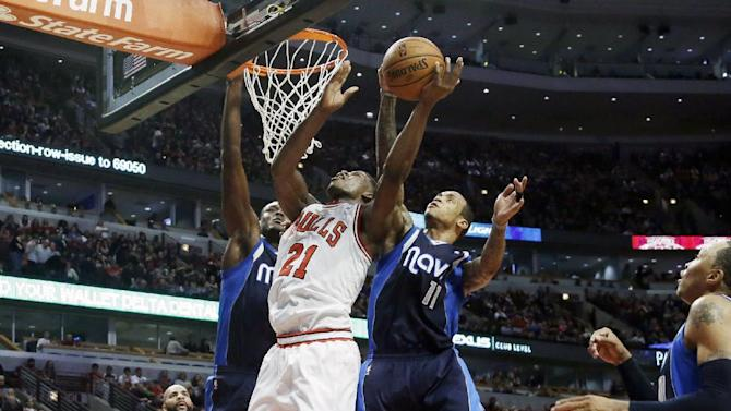 Chicago Bulls guard Jimmy Butler, center, drives to the basket against Dallas Mavericks center Samuel Dalembert, left, and guard Monta Ellis during the second half of an NBA basketball game in Chicago on Saturday, Dec. 28, 2013. The Mavericks won 105-83