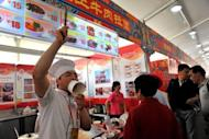 This file photo, taken in May, shows a vendor calling out to customers at a food court in Beijing. China's inflation rate eased to 3.0 percent in May, its lowest level since June 2010, according to latest official data, giving the government further room to loosen credit to boost flagging growth