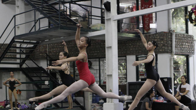 In this photo taken Nov. 25, 2012, Filipino slum dweller Jessa Balote, center, practices with other students during a class at Ballet Manila in the Philippine capital. Balote, who used to tag along with her family as they collect garbage at a nearby dumpsite, is a scholar at Ballet Manila's dance program. As an apprentice, she makes around 7,000 pesos ($170) a month, sometimes double that, from stipend and performance fees. (AP Photo/Aaron Favila)