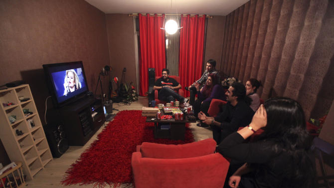 "In this picture taken on Monday, Feb. 4, 2013, members of an Iranian band called ""Accolade"" and their friends watch a performance of British singer Adele, following their training session at the house of one of their members in Tehran, Iran. Headphone-wearing disc jockeys mixing beats. It's an underground music scene that is flourishing in Iran, despite government restrictions. (AP Photo/Vahid Salemi)"