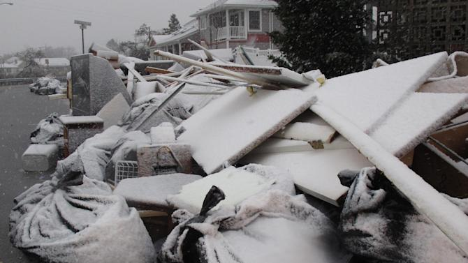 Snow covers debris piles as flood waters start to return to neighborhoods in Point Pleasant Beach, N.J.,  Wednesday Nov. 7, 2012, as a nor'easter hits. The storm was threatening new damage to areas of the Jersey shore already devastated last week by Superstorm Sandy. (AP Photo/Wayne Parry)