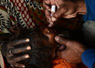 A Pakistani polio vaccination worker gives polio vaccine drops to a young child in a slum area of Lahore on December 21, 2012. Pakistan is providing paramilitary and police support to polio vaccinations being resumed discreetly in the northwest after a series of attacks on medical workers, officials said Friday