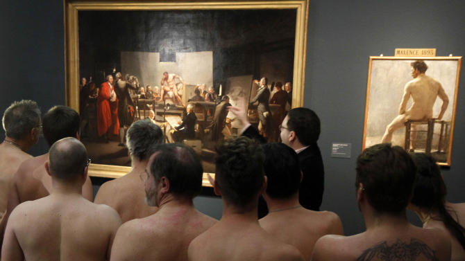 """RETRANSMISSION  OF XRZ102 In this Monday, Feb. 18, 2013 photo, Naked Museum visitors look at pictures of the show """"Nude Men from 1800 to Today"""" during a special opening to friends of nudism at the Leopold Museum, Vienna, Austria. The show """"Nude Men from 1800 to Today"""" opened its doors from 19 October 2012 to  March  4,2013, looking at how artists have dealt with the theme of male nudity over the centuries. (AP Photo/Ronald Zak)"""