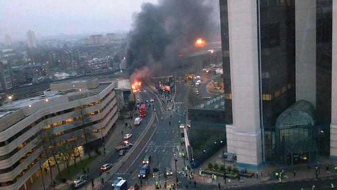 In this overhead view showing smoke and flames at the site of a helicopter crash in central London, as people gather to view the scene shortly after the incident, early Wednesday Jan. 16, 2013. Police say two people were killed when a helicopter crashed during rush hour in central London after apparently hitting a construction crane on the side of St. George's Tower. This photo was taken from an adjacent building to St. George's Tower which is out of shot right, and construction workers are seen gathering below right.  (AP Photo / Victor Jimenez, PA) UNITED KINGDOM OUT - NO SALES - NO ARCHIVES