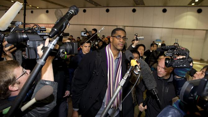 Former NBA basketball star Charles D. Smith, center, is surrounded by journalists upon arrival at the Beijing Capital International Airport in Beijing from Pyongyang, North Korea, Friday, Jan. 10, 2014. A squad of former basketball stars led by Dennis Rodman had a friendly game with North Korean basketball players in Pyongyang