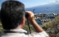 A person looks on with binoculars as the capsized cruise liner Costa Concordia lies on its side next to Giglio Island September 16, 2013. REUTERS/Tony Gentile