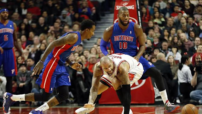 Detroit Pistons guard Brandon Jennings, left, and forward Greg Monroe (10) battle for the loose ball with Chicago Bulls forward Carlos Boozer, center, during the first half of an NBA basketball game in Chicago, Saturday, Dec. 7, 2013