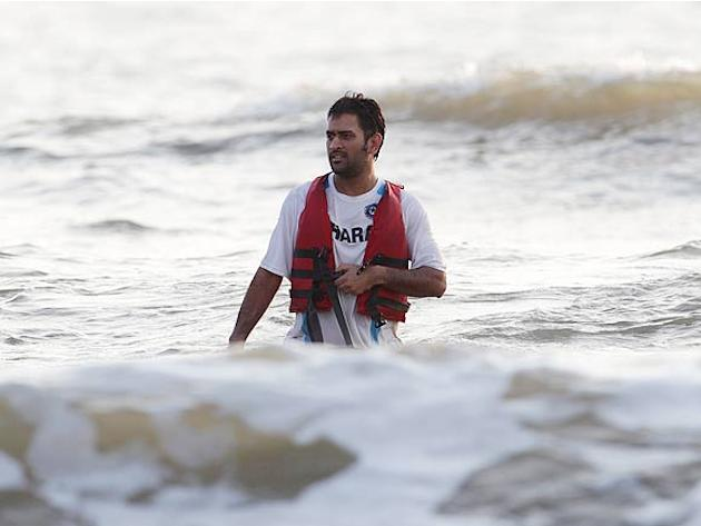 India's captain Mahendra Singh Dhoni walks back to the shore after spending time with wife Sakshi in the Arabian sea after India won the One-Day International match series against Australia by 1-0. (A