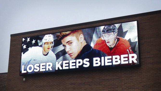 An electronic billboard sign shows U.S. and Canadian hockey players sandwiched between the image of pop star Justin Bieber, on a wall in Skokie