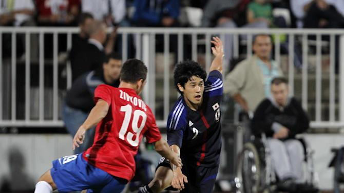 Japan's Atsuto Uchida, centre challenges for the ball with Serbia's Andrija Zivkovic during their international friendly match, at Karadjordje stadium in Novi Sad, Serbia, Friday, Oct. 11, 2013
