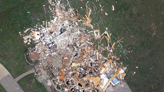 In this aerial photo, a person, lower right, stand in front of a home demolished home by Monday's tornado, in Moore, Okla., Tuesday, May 21, 2013. The huge tornado roared through the Oklahoma City suburb Monday, flattening entire neighborhoods and destroying an elementary school with a direct blow as children and teachers huddled against winds. (AP Photo/Tony Gutierrez)