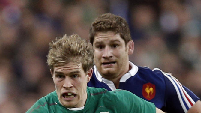 Ireland's Andrew Trimble, front, runs with the ball followed by France's Pascal Pape during the Six Nations Rugby Union match between France and Ireland at the stade de France stadium, in Saint Denis, outside Paris, Saturday, March 15, 2014. (AP Photo/Christophe Ena)
