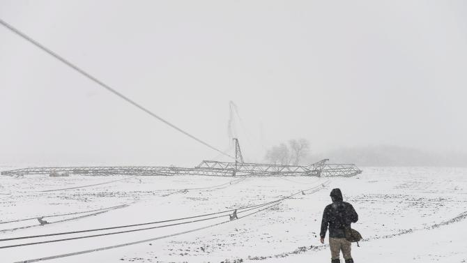 Broken pylons of an electric main lie on the ground near Kemecse, 242 kms east of Budapest, Hungary, after a heavy snowstorm hit the region Friday, March 15, 2013. Winter weather returning to Hungary with heavy snowfall, blizzards, ice and cold has left thousands without electricity, blocked access to several localities, forced traffic halts in major services and caused several accidents across the country.  (AP Photo/MTI, Atilla Balazs)