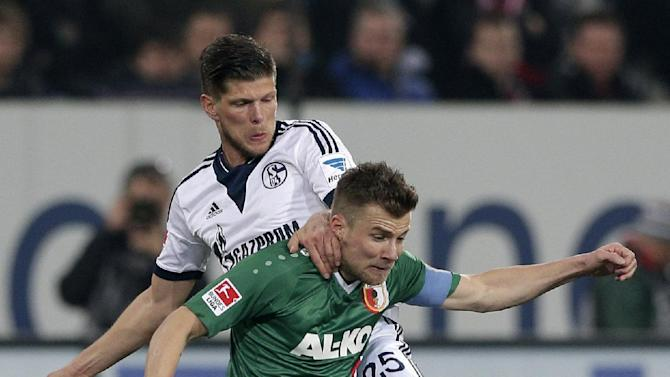 Schalke's Klaas-Jan Huntelaar of the Netherlands, background, and Augsburg's Daniel Baier challenge for the ball during the German first division Bundesliga soccer match between FC Augsburg and FC Schalke 04, in Augsburg, southern Germany, Friday, March 14, 2014