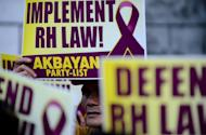 Activists supporting the Reproductive Health (RH) Law hold a protest in front of the Supreme Court building in Manila on March 19, 2013. The Philippines' highest court suspended on Tuesday a controversial birth control law that had met fierce opposition from the powerful Catholic Church