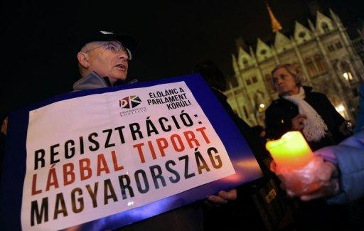 "A participant holds a banner reading, ""Registration: Trampled Hungary"" in front of the parliament building in Budapest. Over a thousand people formed a human chain around the Hungarian parliament building on Monday in protest of a government shake-up of the country's electoral system."