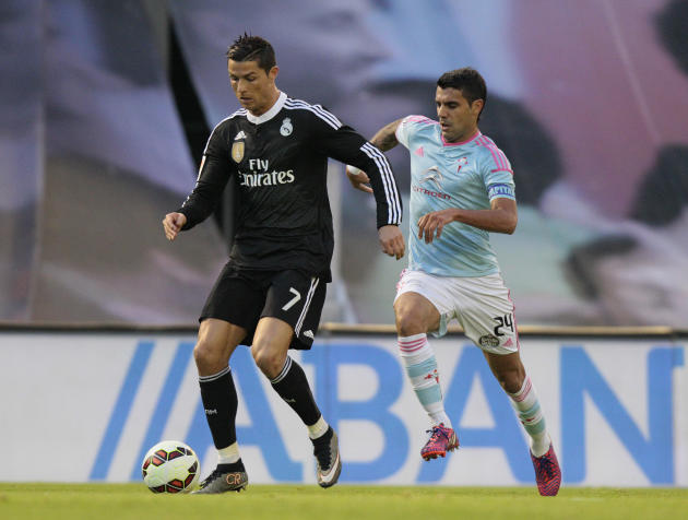Real Madrid's Cristiano Ronaldo from Portugal, left, fights for the ball against RC Celta's Augusto Fernández from Argentina, right, during a Spanish La Liga soccer match between RC Celta and Real