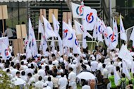 Supporters of the Peolpe's Action Party (PAP) are seen gathering at the nomination center in Singapore, on January 16, 2013. Singapore's ruling party suffered a fresh rebuke from voters on Saturday when it lost a parliamentary by-election despite promises of more reforms to appease a restive electorate