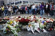 People stand by flowers and candles as they gather on July 23, 2011 in Oslo to mourn and show their respect for the victims of the twin attacks the day before. Anders Behring Breivik, who is set to go on trial on April 16 for killing 77 people in the attacks, said in a letter published Wednesday that being sentenced to psychiatric care would be the worst fate imaginable