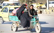 A Syrian woman is driven on a three wheeler auto in Aleppo's old city on January 17, 2013