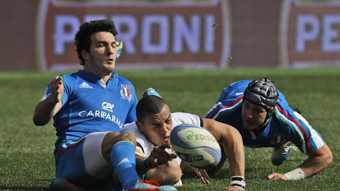 England's Luther Burrell, center, eyes the ball as Italy's Leonardo Sarto, left, and his teammate Michele Campagnaro try to stop him during a Six Nations international rugby union match between Italy and England, in Rome, Saturday, March 15, 2014. Owen Farrell accounted for 22 points and Mike Brown added two tries as England stated its case for the Six Nations title with a convincing 52-11 win over Italy on Saturday at the Stadio Olimpico
