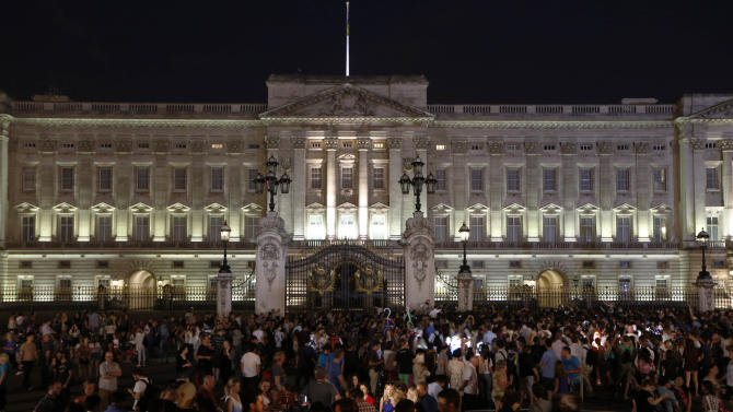 People gather outside a floodlit Buckingham Palace in London to mark the birth of a baby boy to Prince William and Kate, Duchess of Cambridge, Monday, July 22, 2013. (AP Photo/Sang Tan)