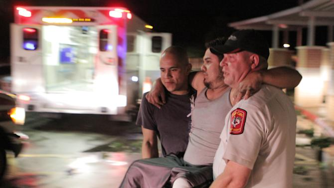 "Johnny Ortiz, left, and James South, right, carry Miguel Morales, center, who was injured in a tornado, to an ambulance in Granbury, Texas, on Wednesday May 15, 2013. Officials report the tornado caused ""multiple fatalities"" as it tore through two neighborhoods of a North Texas town. Hood County sheriff's Lt. Kathy Jiveden reported the multiple fatalities, but she had no estimate of dead or injured. (AP Photo/Mike Fuentes)"