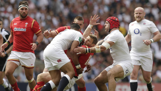 Wales' Dan Biggar in action with England's Luther Burrell and James Haskell