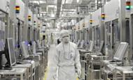 This file photo shows an employee of Japan's microprocessor maker Renesas Electronics at the company's Naka wafer fabrication factory in Hitachinaka, Ibaraki prefecture, in 2011. Renesas is considering cutting up to 14,000 jobs or 30 percent of its workforce as part of a major restructuring plan, according to the latest news reports