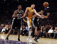 Josh McRoberts (C) of the Los Angeles Lakers goes for a rebound between Tony Parker (R) and Boris Diaw (L) of the San Antonio Spurs during their game on April 17. The Spurs won 112-91