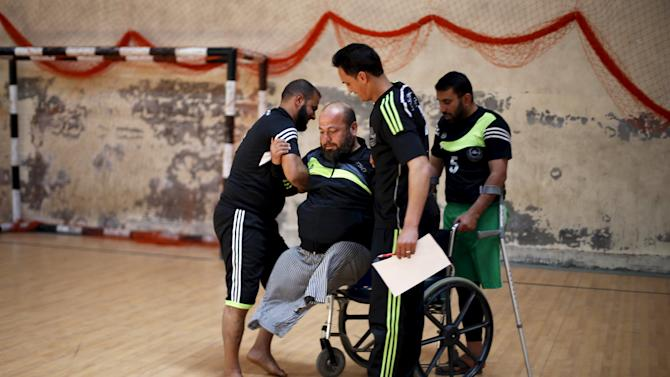 Disabled Palestinian Asker, who said that he lost his limbs in an Israeli air strike in 2004, is helped out of his chair as he arrives to take part in a local sitting volleyball championship in Gaza City