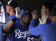 Kansas City Royals' Melky Cabrera (53) is congratulated by teammates in the dugout after hitting a solo home run in the first inning of an interleague baseball game against the Colorado Rockies in Denver on Sunday, July 3, 2011. (AP Photo/Chris Schneider)