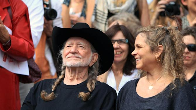 Country singer Willie Nelson and his wife, Annie D'Angelo Nelson look on during the unveiling of an eight-foot statue of himself, Friday, April 20, 2012 in Austin, Texas. The privately-funded monument near the new Moody Theater shows Nelson in a relaxed, standing pose and holding his guitar to the side, as if in conversation.  (AP Photo/Austin American-Statesman, Jay Janner)  MAGS OUT; NO SALES; INTERNET AND TV MUST CREDIT PHOTOGRAPHER AND STATESMAN.COM
