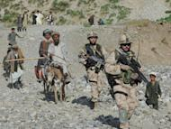 NATO-led International Security Assistance Force (ISAF) soldiers walk with Afghan villagers during a search for victims following an earthquake in a village in Baghlan province on June 12. Iran on Thursday warned a key international conference that a long-term US military presence in Afghanistan would fan regional insecurity and could plunge the war-torn country back into further chaos
