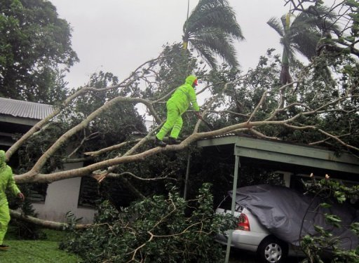 Residents clear away branches from a tree that collapsed outside a house in Suva on December 17, 2012. Tropical Cyclone Evan left a swathe of destruction across Fiji Tuesday after battering the Pacific nation for more than 12 hours, destroying homes, flooding rivers and stranding thousands of tourists.