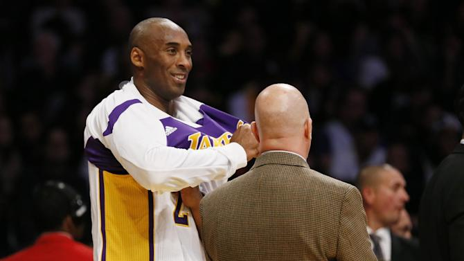 Los Angeles Lakers' Kobe Bryant, left, talks with athletic trainer Gary Vitti, as he comes out of the first quarter of an NBA basketball game against the Toronto Raptors in Los Angeles, Sunday, Dec. 8, 2013. It was Bryant's first game back after a torn left Achilles tendon injury on April 12th