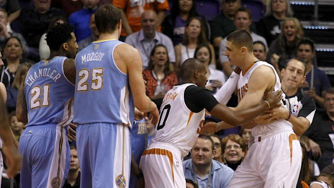 Phoenix Suns center Alex Len (21) gets held back from Leandro Barbosa (10) after getting into a shoving match with players of the Denver Nuggets in the first quarter during an NBA basketball game, Sunday, Jan. 19, 2014, in Phoenix