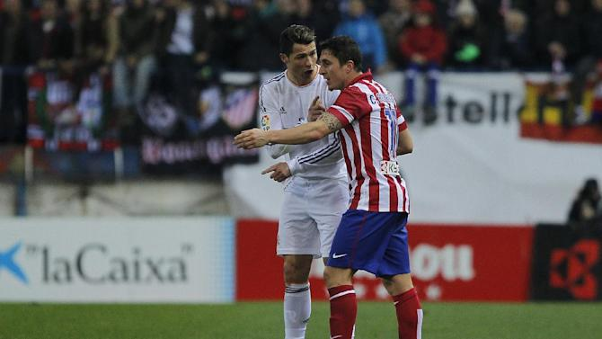 Real's Cristiano Ronaldo discuss with Atletico's Cristian Rodriguez, after Ronaldo fouls Atletico's Javi Manquillo during a semi final, 2nd leg, Copa del Rey soccer match between Atletico de Madrid and Real Madrid at the Vicente Calderon stadium in Madrid, Spain, Tuesday, Feb. 11, 2014