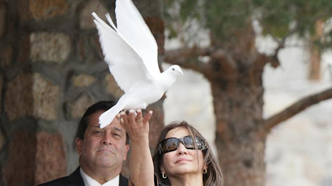 """Flora Enchinton Bernal releases a white dove during a graveside service for actor Sherman Hemsley, Wednesday, Nov. 21, 2012 in Fort Bliss, Texas. Friends and family remembered Hemsley at his funeral service in Texas by showing video clips of his best known role as George Jefferson on the TV sitcom """"The Jeffersons."""" He died in July but a fight over his estate has delayed his burial. (AP Photo/The El Paso Times, Mark Lambie)  EL DIARIO OUT; JUAREZ MEXICO OUT AND EL DIARIO DE EL PASO OUT"""
