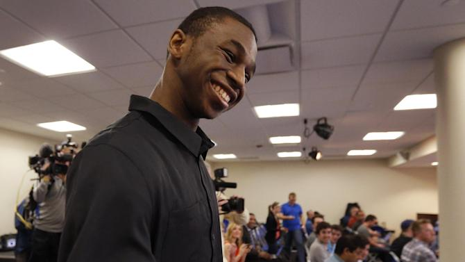 Kansas freshman NCAA college basketball player Andrew Wiggins smiles at teammates before a news conference at the University of Kansas in Lawrence, Kan., Monday, March 31, 2014. Wiggins announced he would be entering the NBA draft