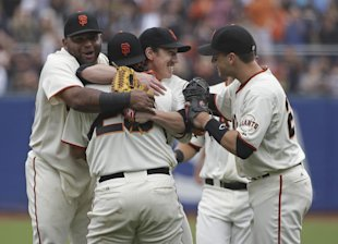 Tim Lincecum, center, is embraced by teammates, from left, Pablo Sandoval, catcher Hector Sanchez, and Buster Posey. (AP)